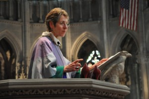 Presiding Bishop Katharine Jefferts Schori during her sermon at Church of the Advocate uses a pair of red high heels to illustrate the expectations set upon ordained women. Photo: Mary Frances Schjonberg/Episcopal News Service www.anglicannews.org